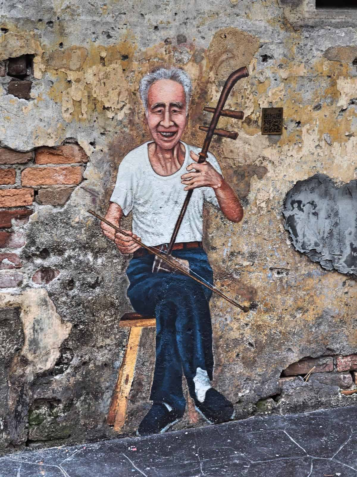A mural of an uncle playing the erhu : Kwai Chai Hong heritage lane in Kuala Lumpur's Chinatown